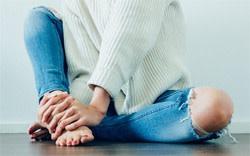A tired nurse massaging her feet after a long shift