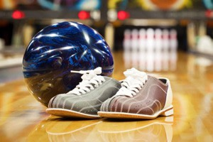 A pair of bowling shoes near a ball