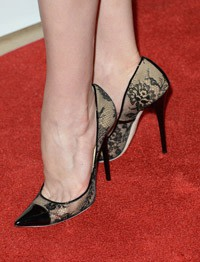 A woman wearing extremely high heeled shoes